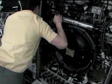 Flight Engineer Tom Marshburn peers<br /> into the inner workings of the<br /> Combustion Integrated Rack as he<br /> performs maintenance on the facility.<br /> Credit: NASA TV